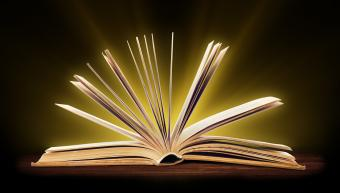 An open book with glowing light coming from the pages