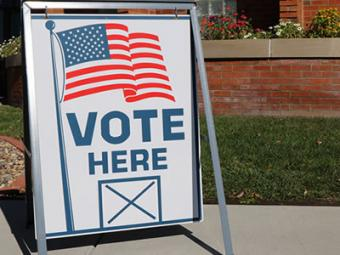 """Sign reading """"Vote Here""""."""