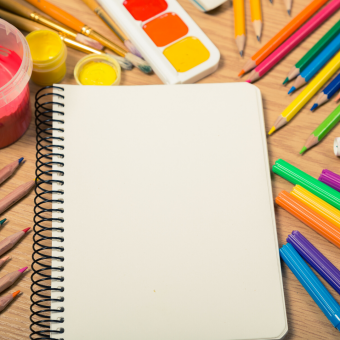 Blank notebook surrounded by craft supplies, including paint and colored pencils