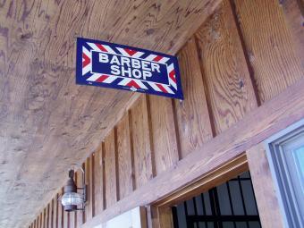 Barber shop sign hangs outside the door.