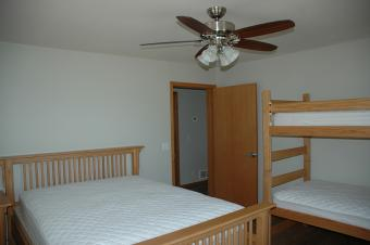 A bedroom at Summit Cabin with a queen bed and twin bunk beds.