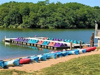 Multiple kayaks accress the sand portage with paddleboats parked at the dock on the lake.
