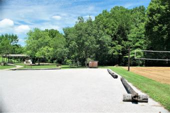 View of picnic shelter, large parking area and sand volleyball court.