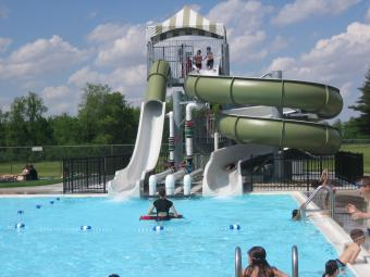 Swimmers having fun at the water slide at Scott County Park Pool.