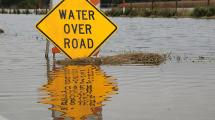 Water Over Road warning sign surrounded by flood waters.