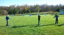 Students lining up bow and arrow on a target.