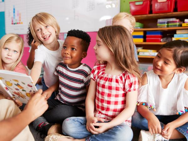 This is a picture of children sitting on the floor listening to a story
